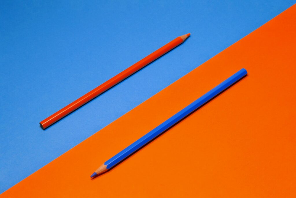diagonally, a red pencil on a blue background and a blue pencil on a red background